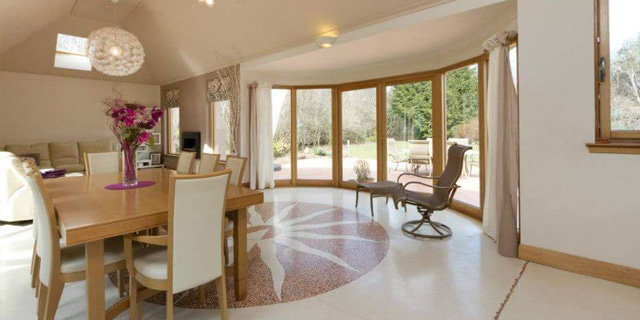 A magnificent, double-height open plan kitchen, dining and living area with opulent 'venetian-style' flooring.