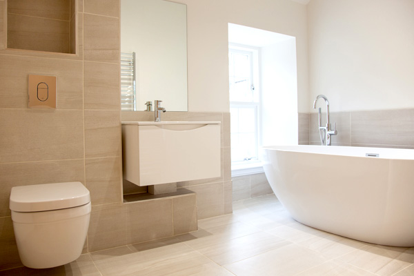 Family bathroom with porcelain tiling and free standing bath.